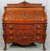 Heavily carved oak slant front secretary by Horner