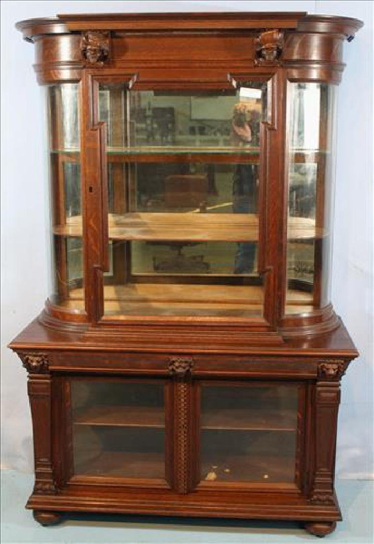 Solid oak china cabinet with heads carved at top