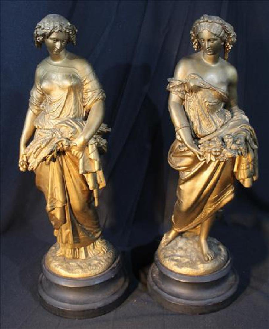 Pair Spelter figurines in gold on black wood base