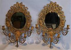 Pair of brass mirrored sconces with faces