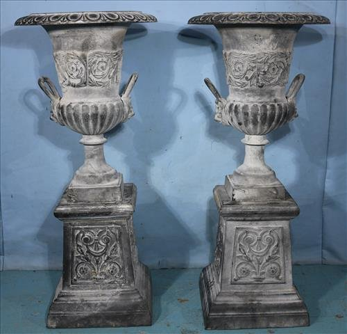 Pair of cast iron urns with handles and base, 41 in T.