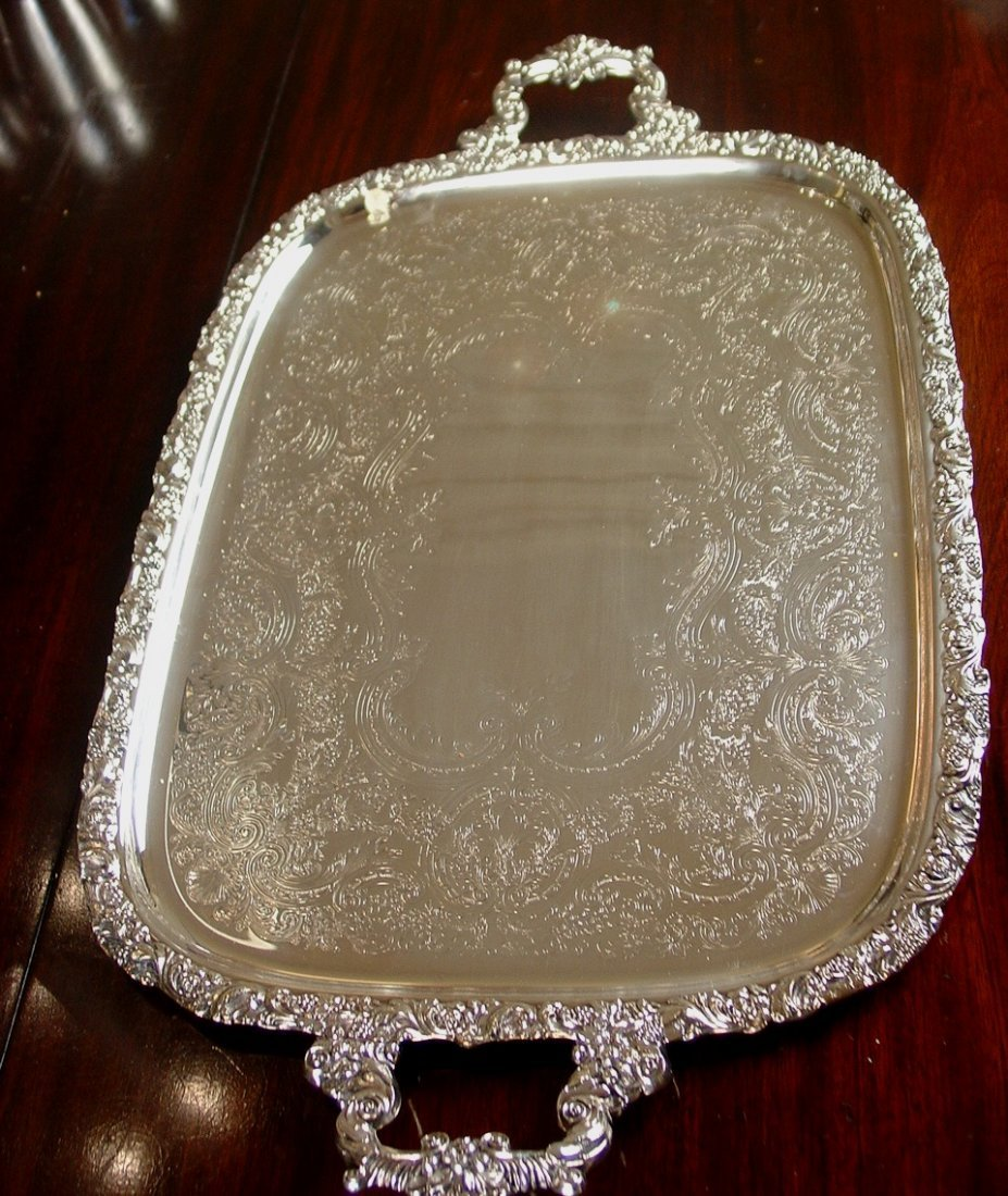 Silver serving tray with ornate handles and engraving,