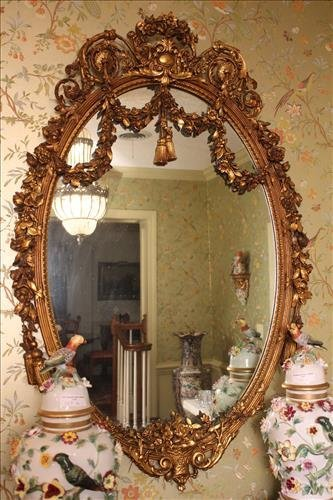 French oval heavily decorated antique mirror