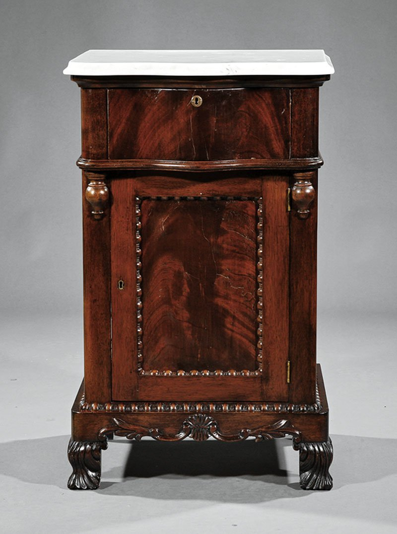 An American Rococo Carved Mahogany Bedside Commod