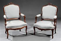 A Pair of Louis XVStyle Carved Walnut Fauteuils