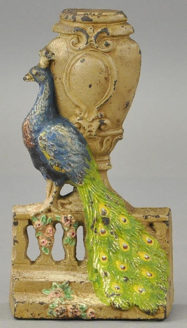 HUBLEY PEACOCK BY URN ON FENCE DOORSTOP