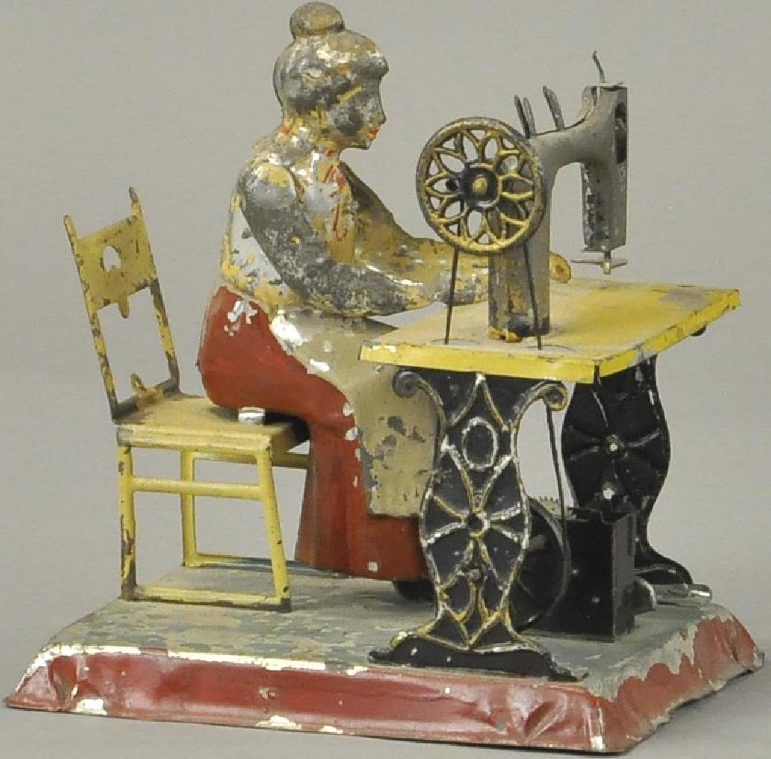 GERMAN TIN GIRL SEATED AT SEWING MAHINE