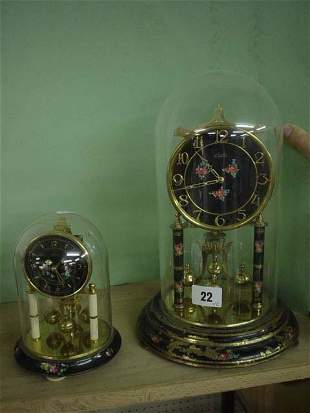Two ornate clocks under glass domes, larger one 1