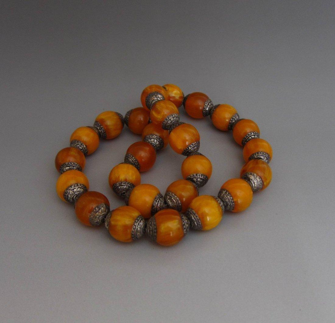 An Antique Tibetan Amber Buddha Bracelet