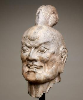 LARGER THAN LIFE-SIZED HEAD OF A GUARDIAN GOD