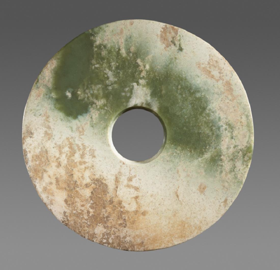 A LARGE SMOOTH BI DISC IN GREEN JADE WITH WHITENED