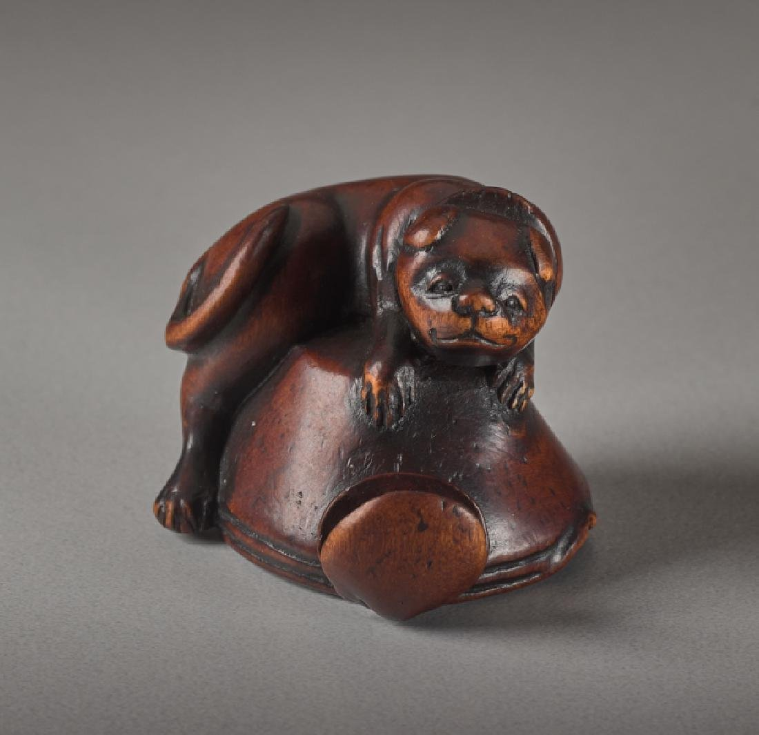 A WOOD NETSUKE OF A DOG AND OCTOPUS