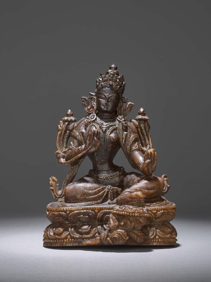 A RARE CARVING OF A GREEN TARA, 17TH CENTURY