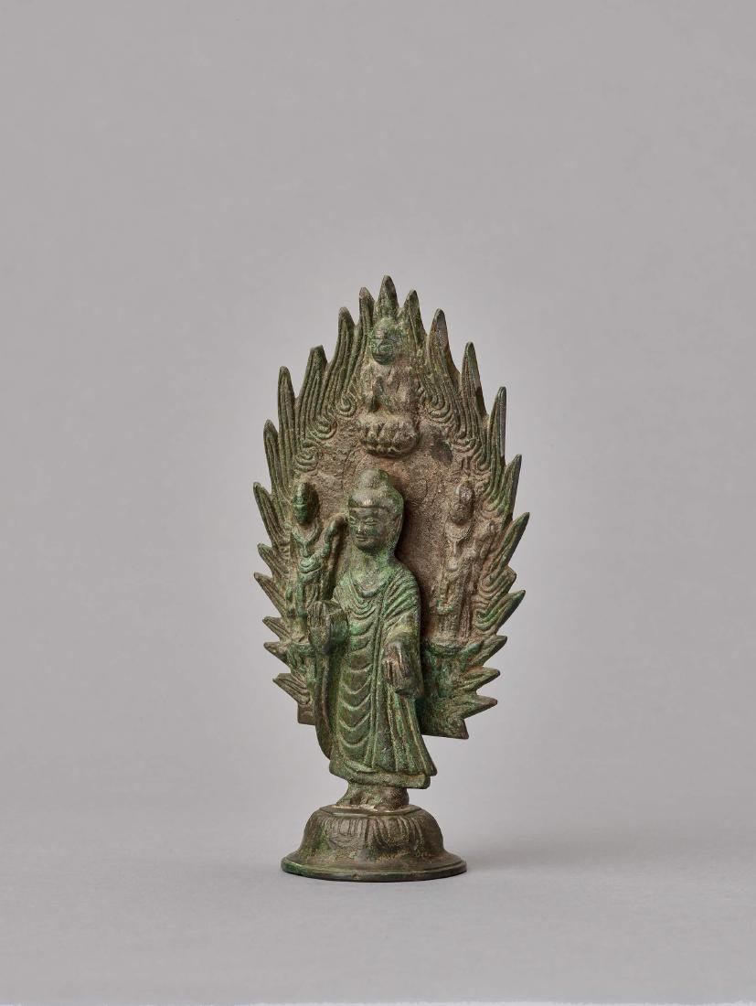 A BRONZE BUDDHA IN FRONT OF A FLAMING HALO, DATED 571