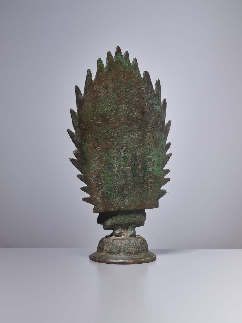 A BRONZE BUDDHA IN FRONT OF A FLAMING HALO, DATED 571 - 5
