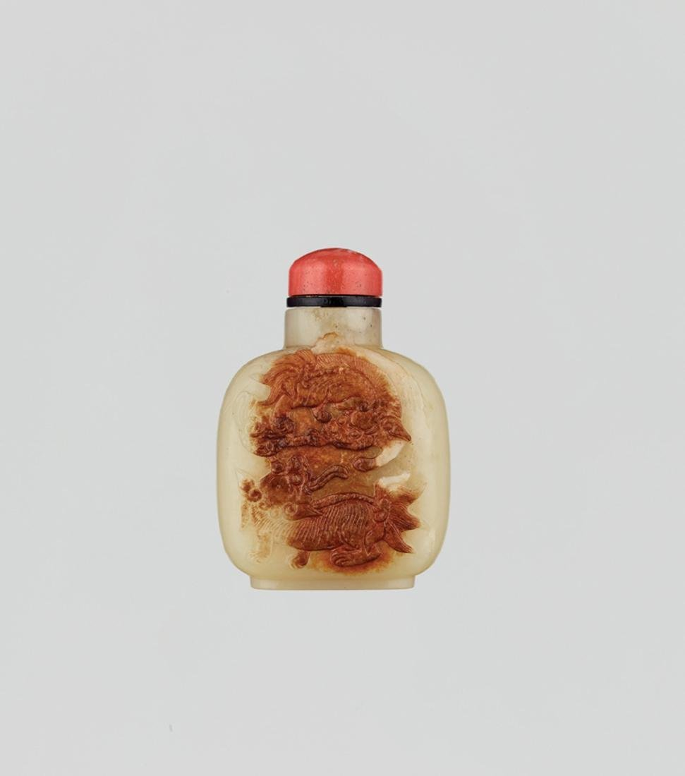 A YELLOW AND RUSSET JADE 'BUDDHIST LION' SNUFF BOTTLE