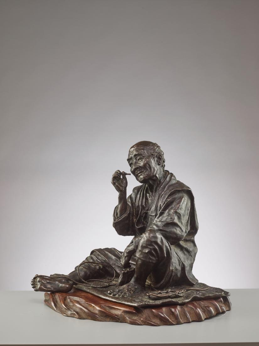 A LARGE BRONZE OF A SANDAL MAKER BY TAKAHASHI RYOUN