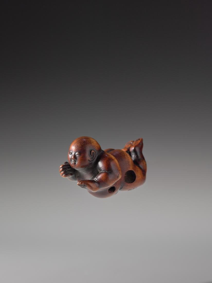 A RARE WOOD NETSUKE OF AN INFANT BOY BY MASAKAZU