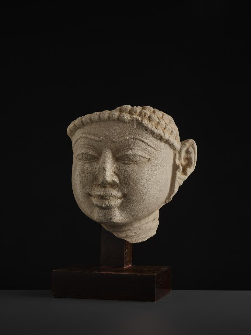 A SANDSTONE HEAD OF A TIRTHANKARA