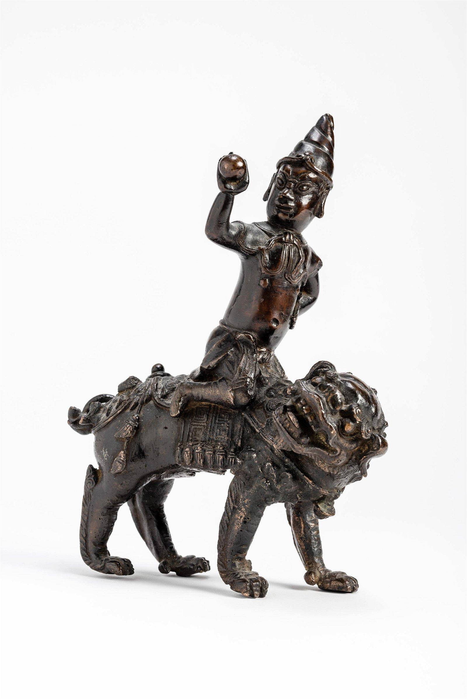 A BRONZE GUARDIAN DEITY RIDING ON A LION