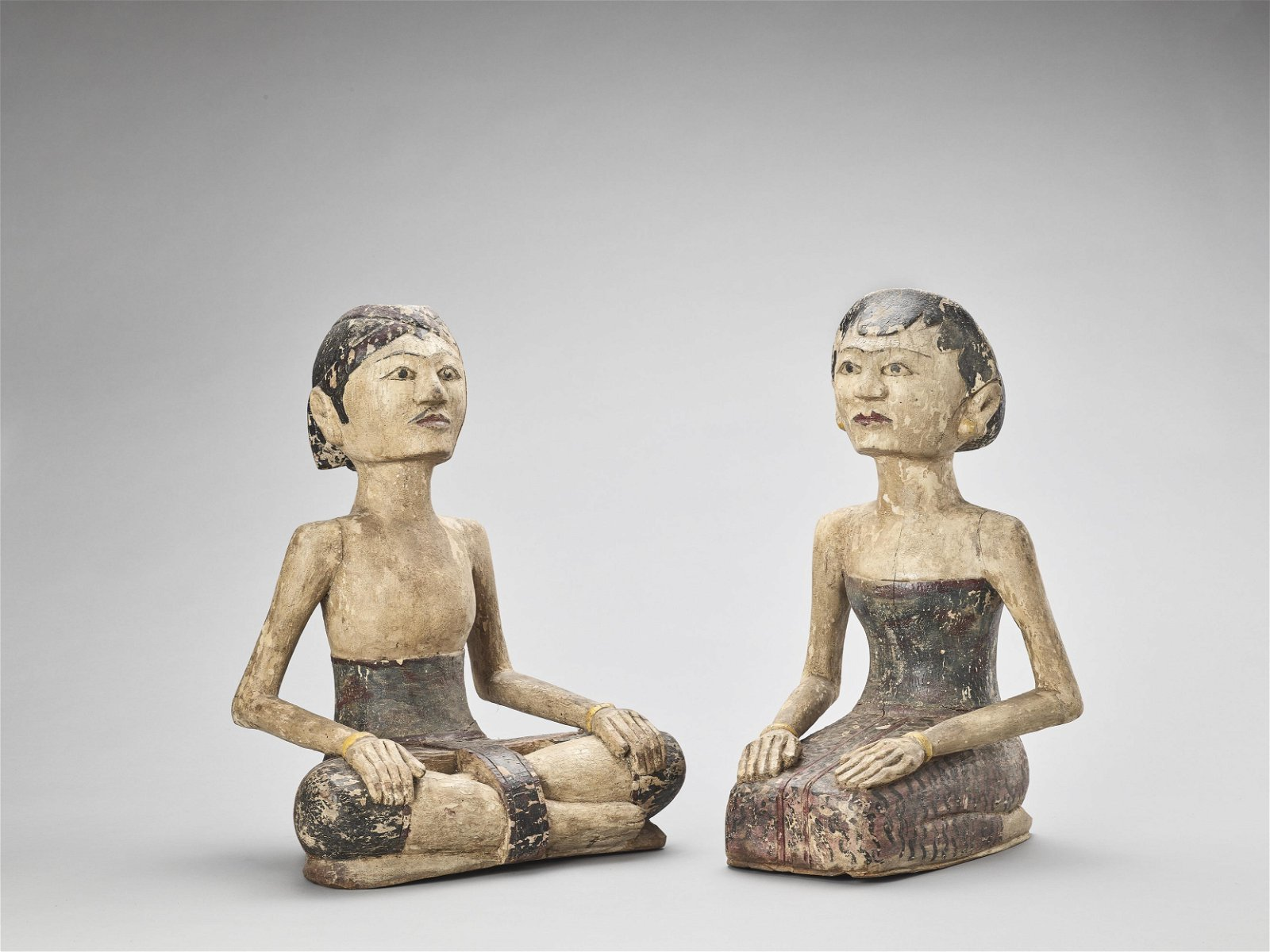 TWO JAVANESE CARVED AND LACQUERED WOOD WORSHIPPERS, LAT