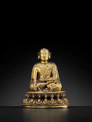 A TIBETAN GILT-BRONZE FIGURE OF A LAMA, 13TH-14TH