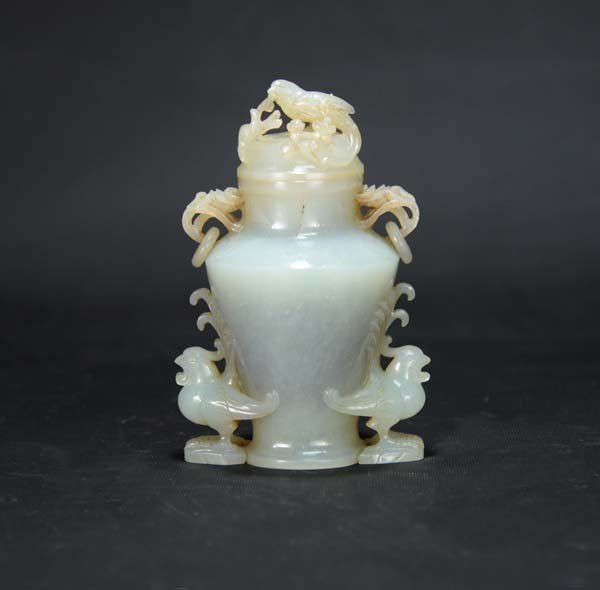 A jade bottle with carving of birds on flowers