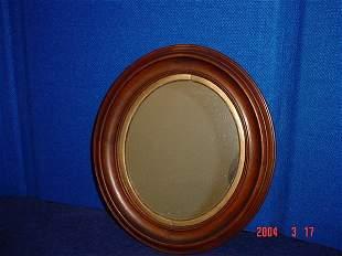 Oval wood framed mirror.