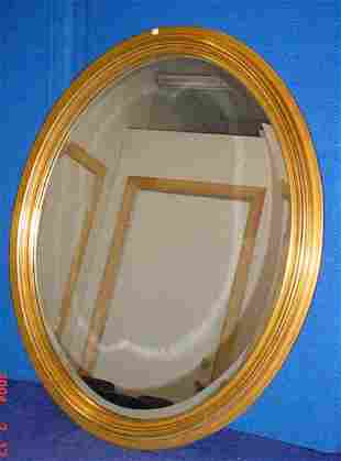 Gold tone oval beveled mirror.