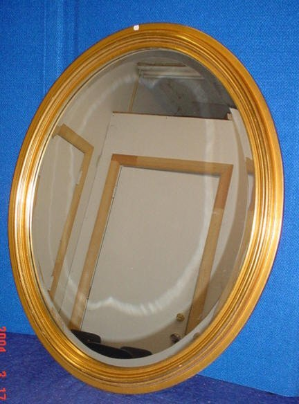 513: Gold tone oval beveled mirror.