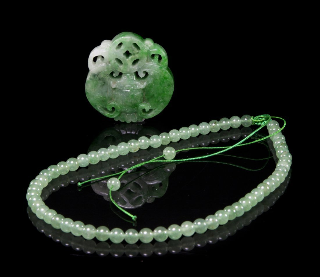 A CARVED JADE PENDANT WITH A STRAND OF A JADE BEADS