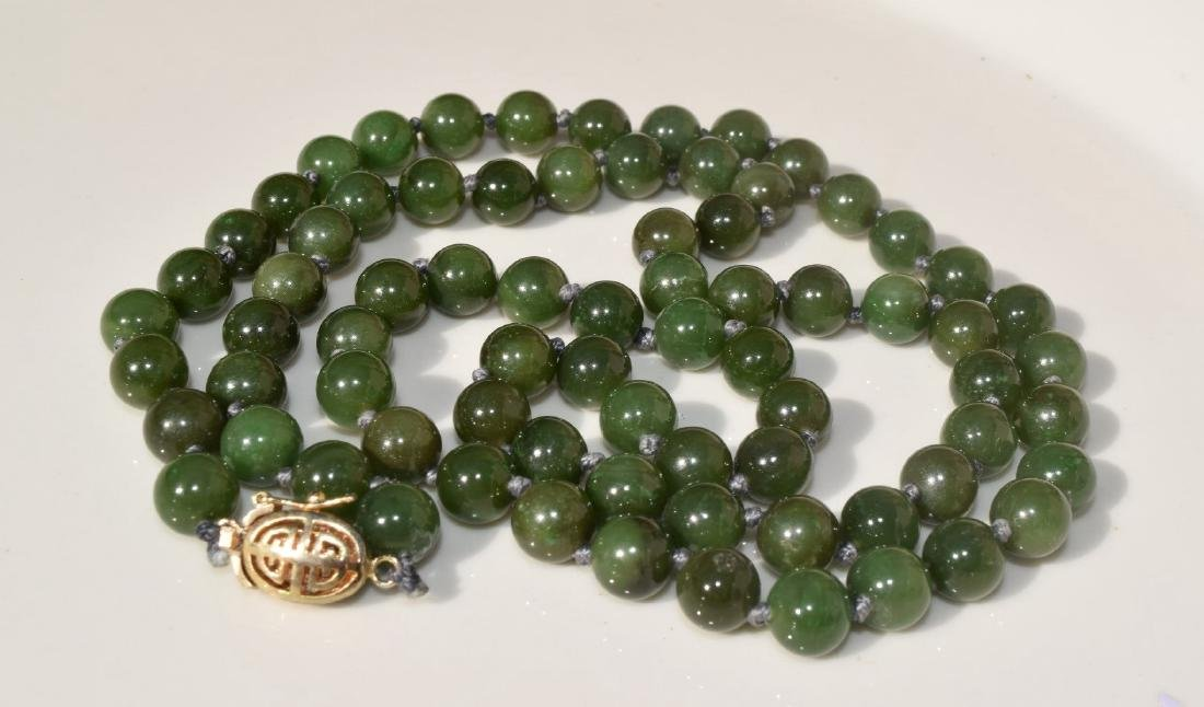 A NEPHRITE GREEN BEAD NECKLACE