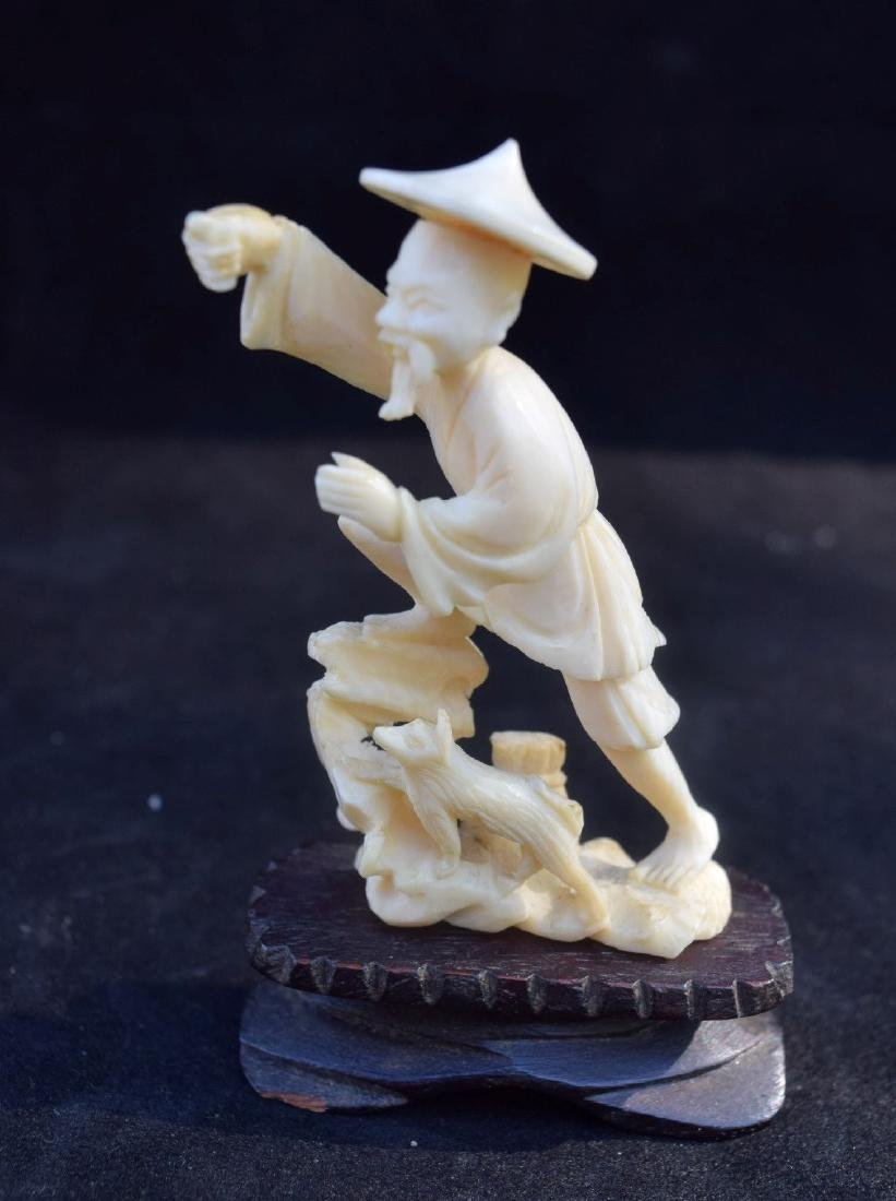 A CARVED FISHERMAN STATUE