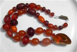 A Chinese Butter Scotch Amber necklace w Peach Pendant