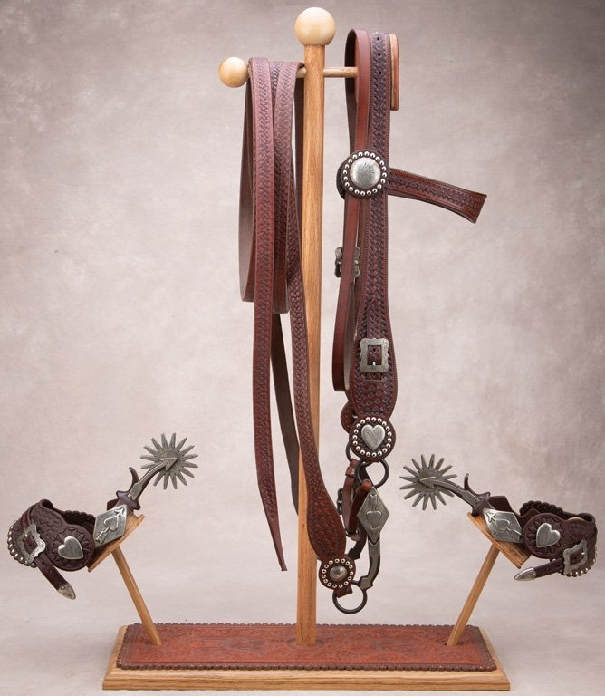 A unique wooden and tooled leather Bridle and Spur