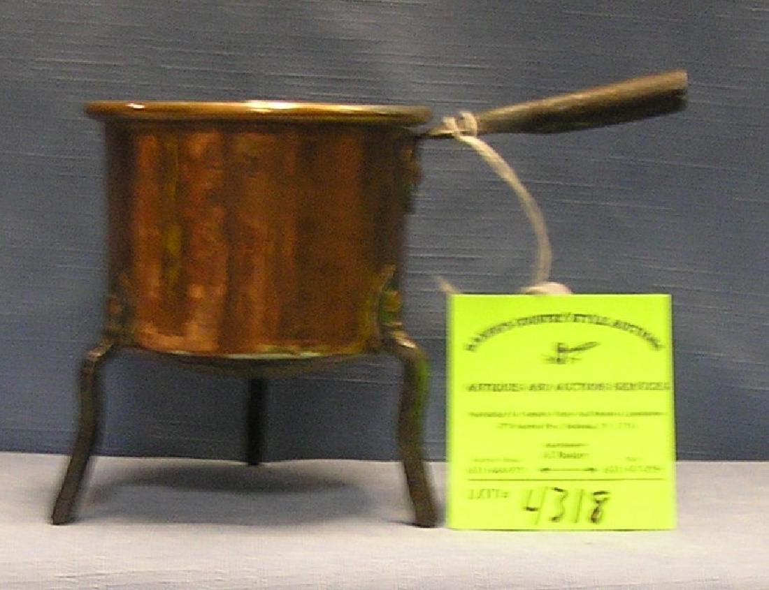 Antique copper kettle with cast iron legs and handle
