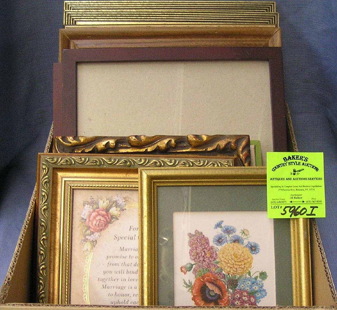 Box full of vintage picture frames some with artwork