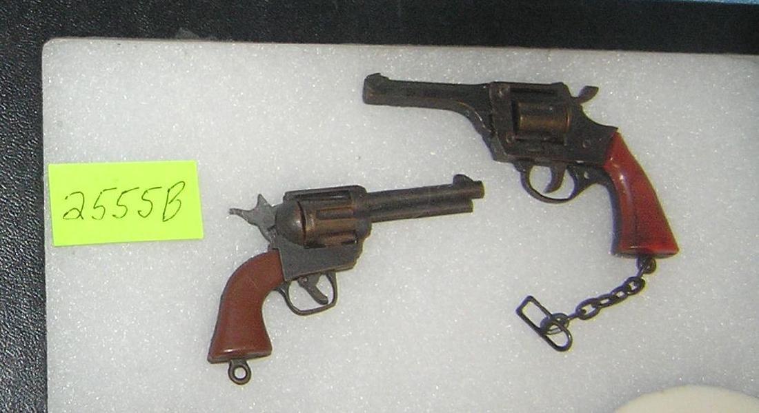 Pair of cast metal miniature cap revolovers