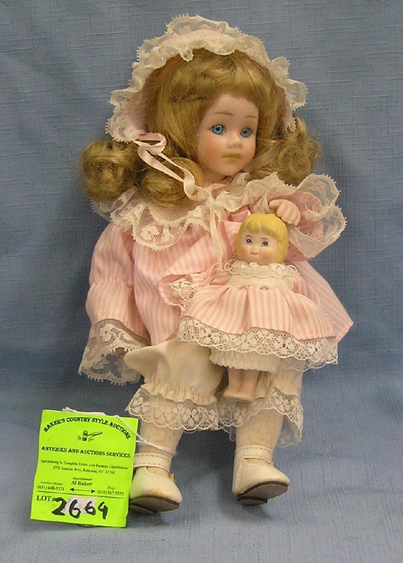 Vintage porcelain child doll clutching a doll