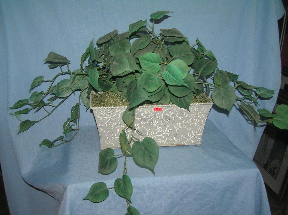 Large artificial plant in decorative tin flower pot