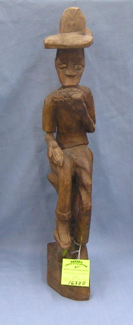 Hand carved African male figure eating corn