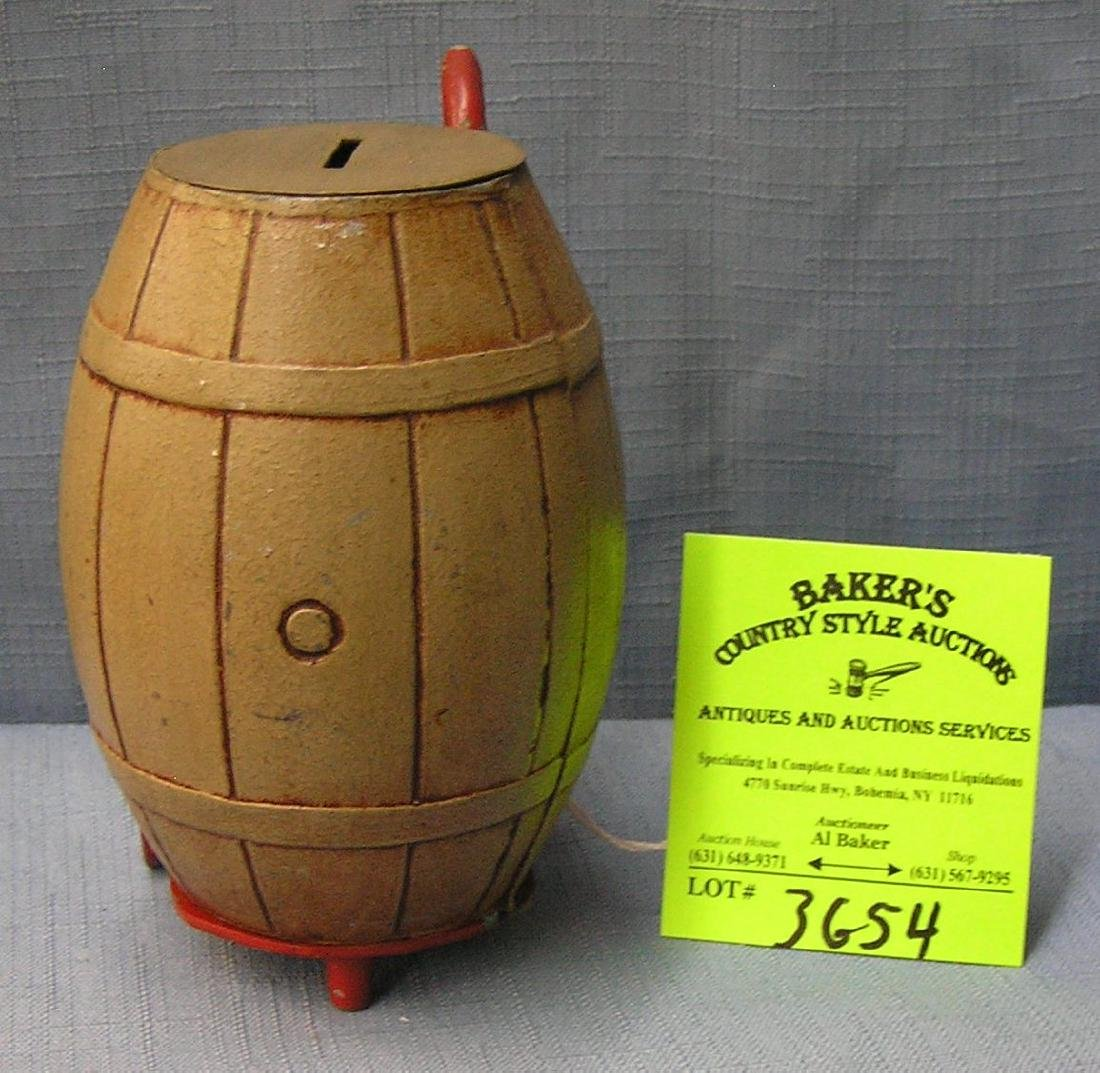 Vintage cast metal barrel and hand truck bank