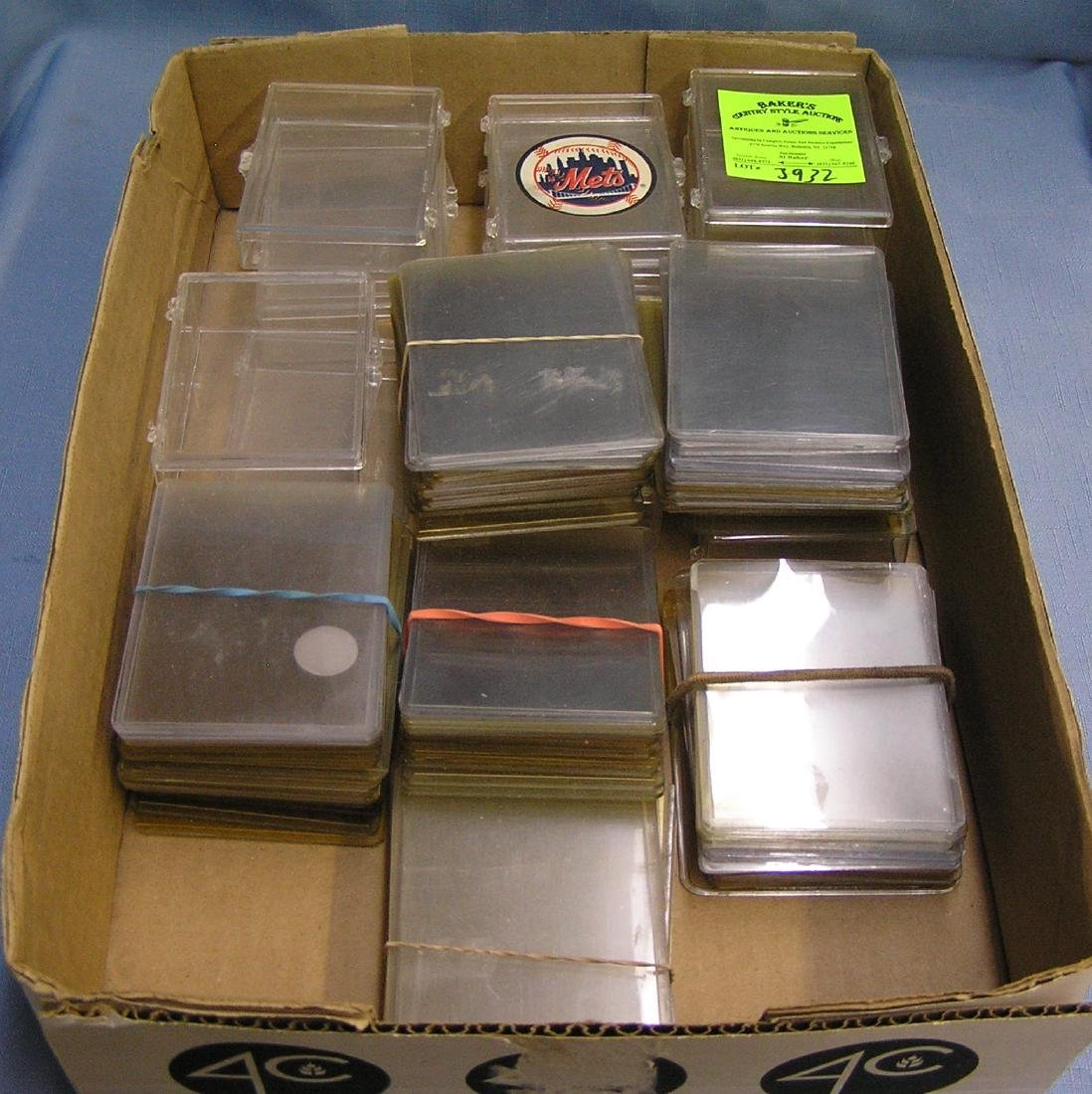 Box full of trading card protective cases and sleeves