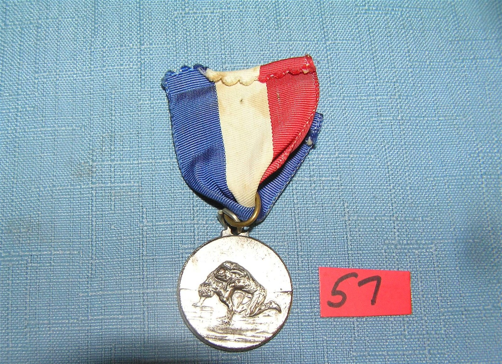 Antique silver toned wrestling medal and ribbon