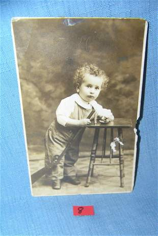 Early photo post card featuring a young boy with toys