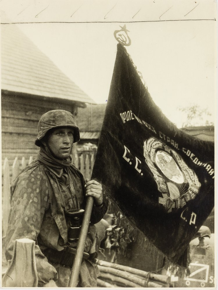WAFFEN-SS SOLDIER WITH CAPTURED RUSSIAN FLAG