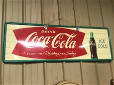 Large metal sign advertising Coca Cola with the