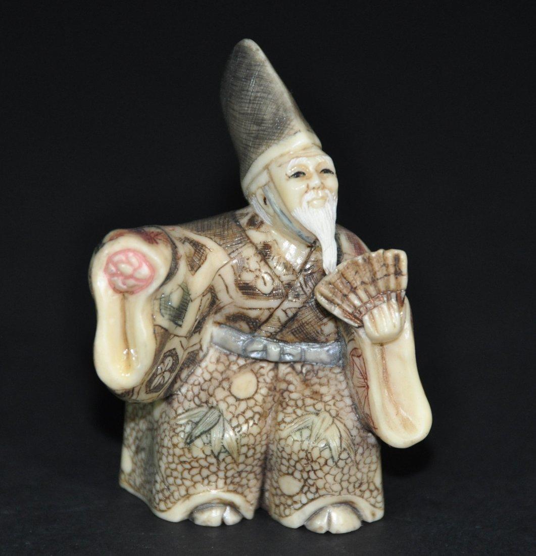 A Japanese carved figural old man