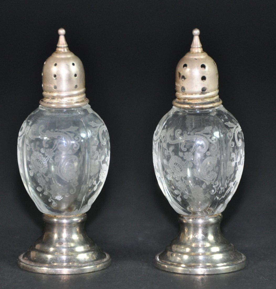 A pair of antique crystal and silver pepper botters