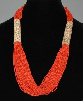 A coral beaded necklace with bone decorations